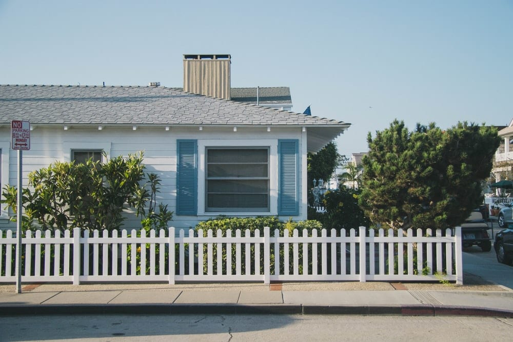 White fence in front of a white and blue house